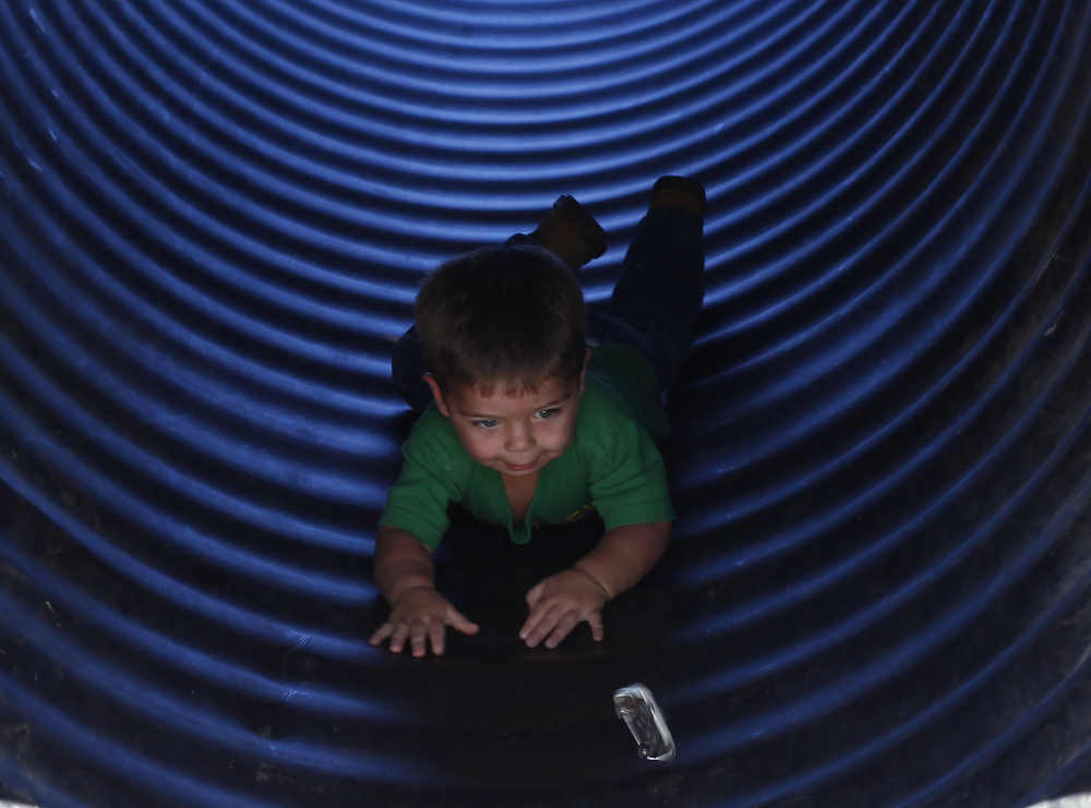 Logan Buck, 2, finishes the hay bail maze at Cullenook Farms by sliding out.