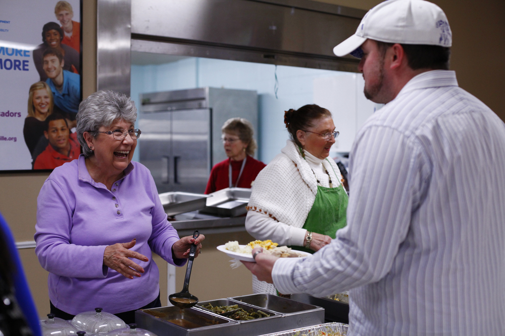 """Wanda Christian serves gravy to community members during the annual Thanksgiving diner that was held at the La Grange Community Center on Saturday. The dinner is free to everyone and is hosted by local churches. """"The denominations come together to feed the people, thats the greatest thing,"""" said Tom Baughman of Beauland Baptist."""