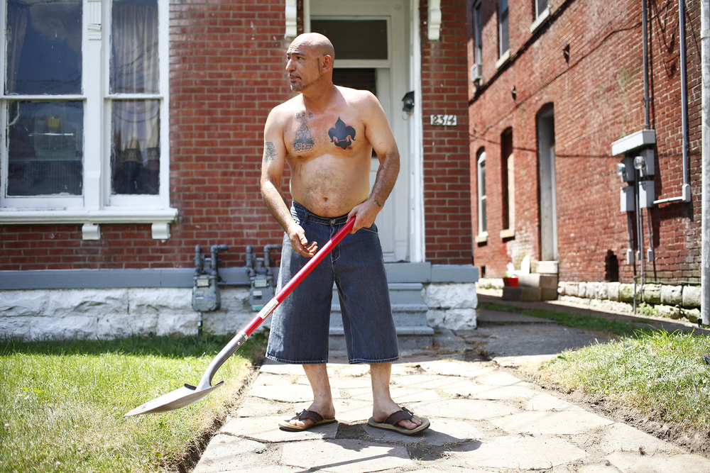 Roger Sutherland, who has lived in Portland for 30 years, cleans grass out of his sidewalk. Sutherland recently got a flour de lis tattooed onto his chest in honor of Louisville.