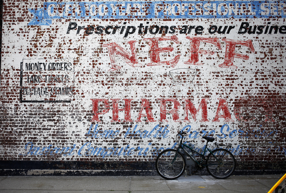 A bike sits in front of an old ad for a local pharmacy on the corner of Portland Avenue and North 25th street.