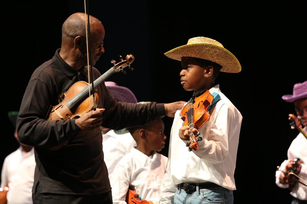Mr. Keith Cook, ArtsReach violin instructor, helps a Young Masters violin student get ready to perform at The ArtsReach Showcase.  For more photos from that night: https://www.flickr.com/photos/kentuckycenter/albums/72157684538345165