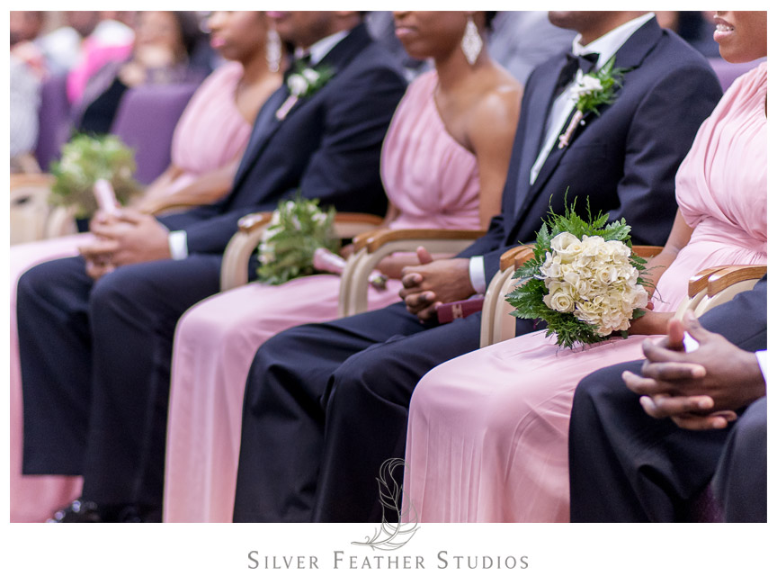 Bridesmaids wear pink one-shoulder dresses, while groomsmen wear black suits.