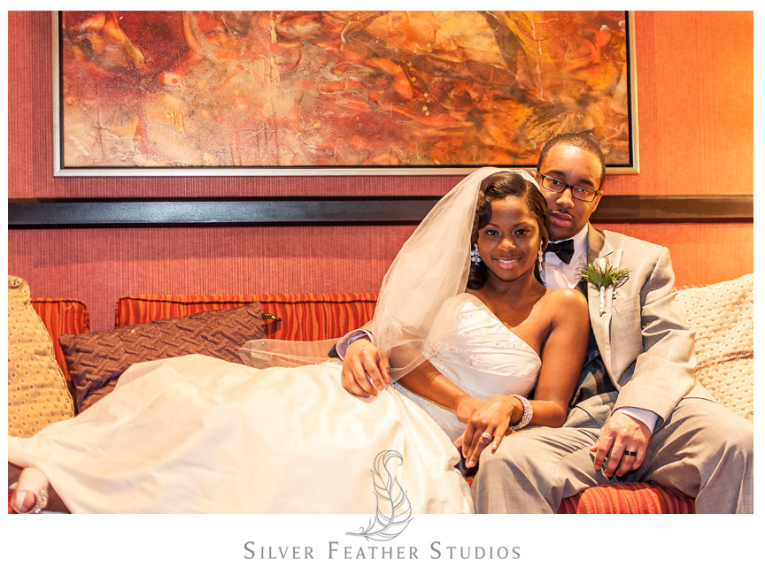The bride & groom pose on a couch at the Marriott Hotel, Conshohocken, Philadelphia.