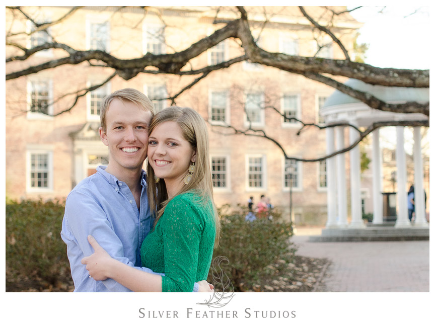Kelly and Hugh pose in front of the Old Well at their UNC Chapel Hill engagement session. © Silver Feather Studios, Chapel Hill Wedding Photography  & Videography