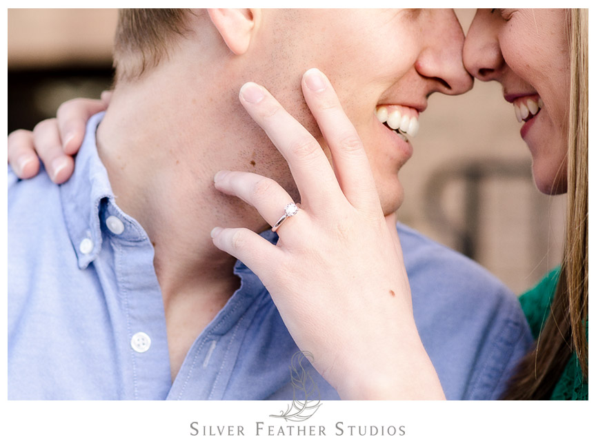 Gorgeous diamond ring on the hand of the bride-to-be on Franklin Street, Chapel Hill. © Silver Feather Studios, Chapel Hill Wedding Videography & Photography