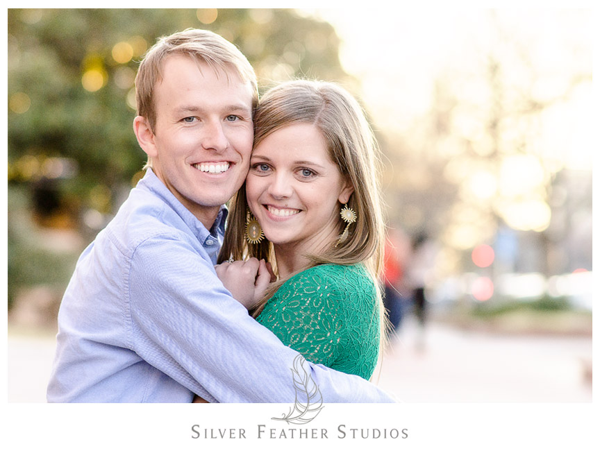 Kelly and Hugh hug on the busy streets of Chapel Hill, North Carolina for their Chapel Hill Engagement Session. © Silver Feather Studios, Chapel Hill Wedding Videography and Photography