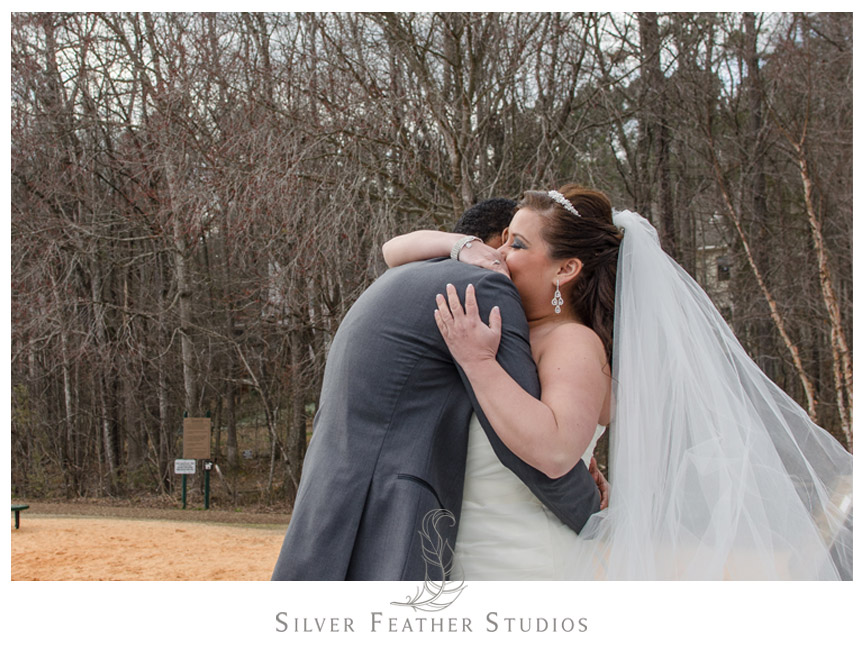 Bride and groom hug during their first look at Bass Lake Park in Holly Springs NC.