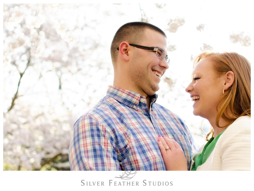 The cherry blossom trees look beautiful behind this couple at their UNC Chapel Hill Engagement session.   © Silver Feather Studios, Chapel Hill Wedding Videography and Photography