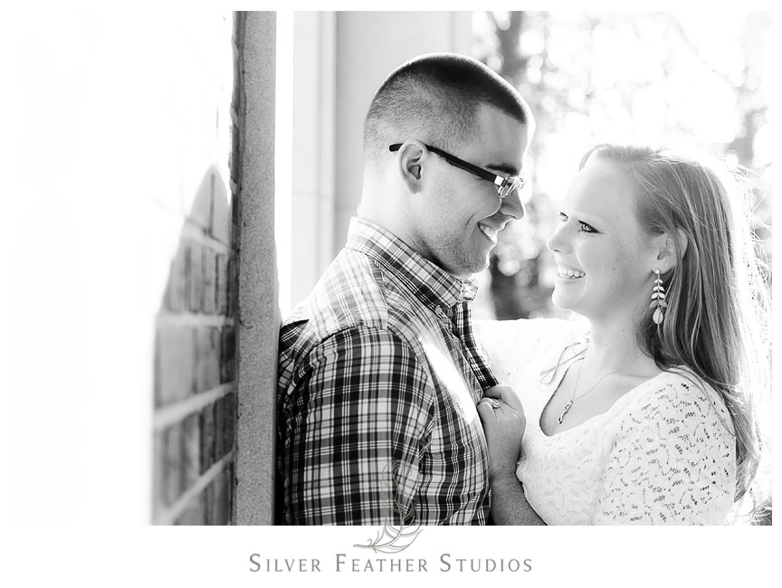Sweet black and white image of Erin and Adam below the bell tower at their UNC Engagement session. © Silver Feather Studios, Chapel Hill Wedding Photography and Videography