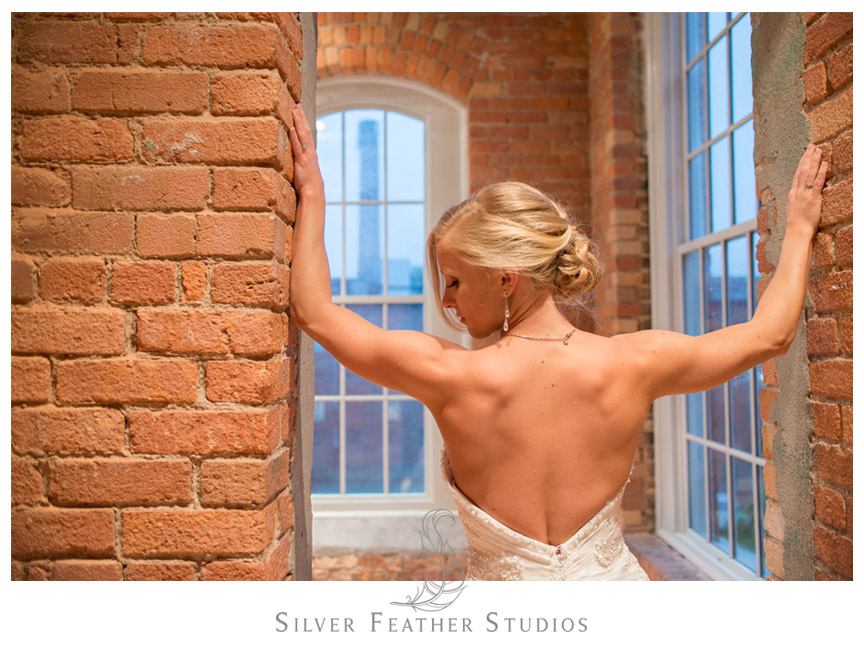 Bride poses in Maggie Sottero gown at The Cotton Room in Durham NC.