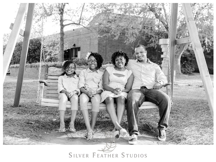 Family pose on bench swing at Elon University Campus.