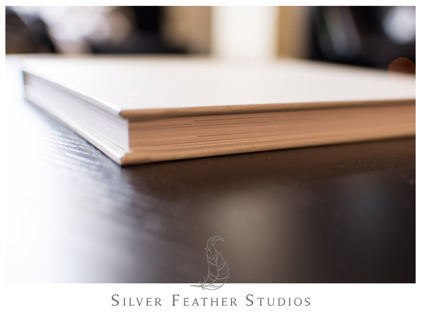 Corner view of cream linen bridal album. Photograph by Silver Feather Studios.