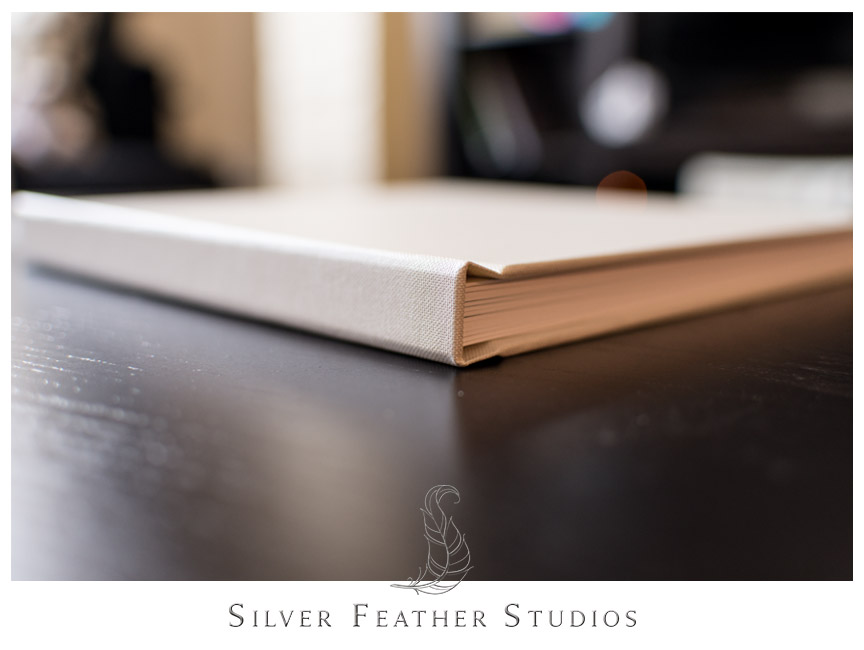 View of binding on a cream linen bridal album. Photograph by Silver Feather Studios.