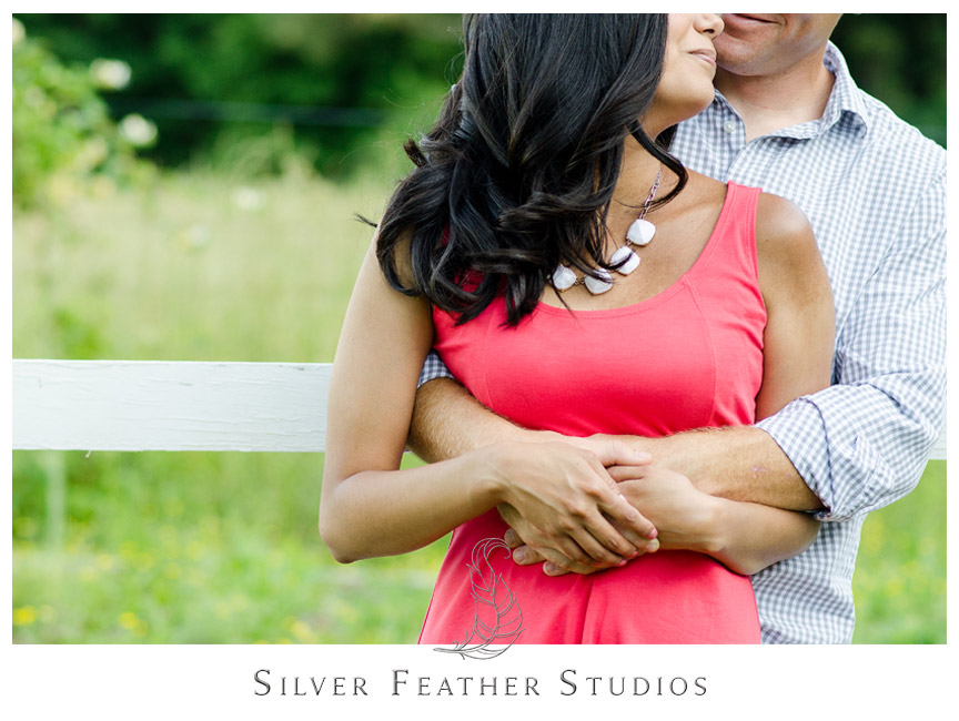 The engaged couple wear a cute coral dress and blue plaid shirt for their photo session.