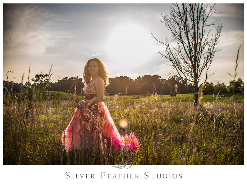 Ariana stands in stunning golden light in fields by Lake Mackintosh