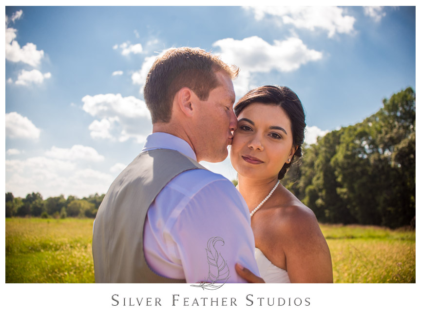 The bride and groom against the blue sky at Starlight Meadow in Burlington, North Carolina.