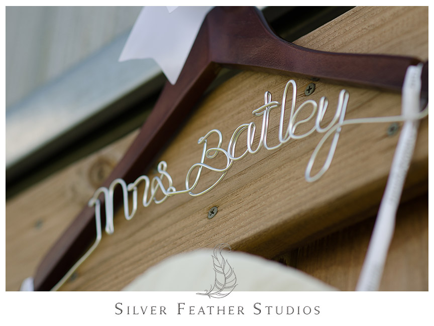 Cute hanger with bride's new last name holds up her stunning wedding gown. Photography by Silver Feather Studios.