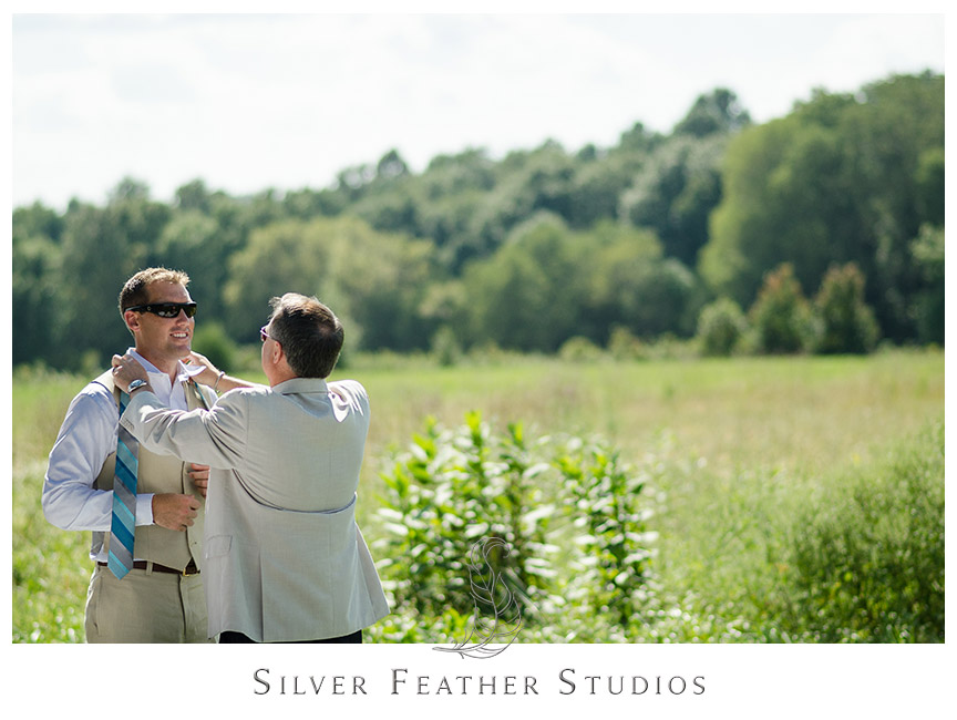 Groom in his tan vest puts on a blue stripe tie for his wedding, by Burlington Wedding photographer.  © Silver Feather Studios
