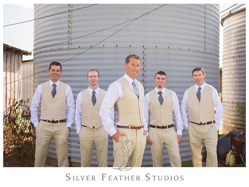 Groom and groomsmen in beige vest and pants with blue ties against a silo at Starlight Meadow.  © Silver Feather Studios