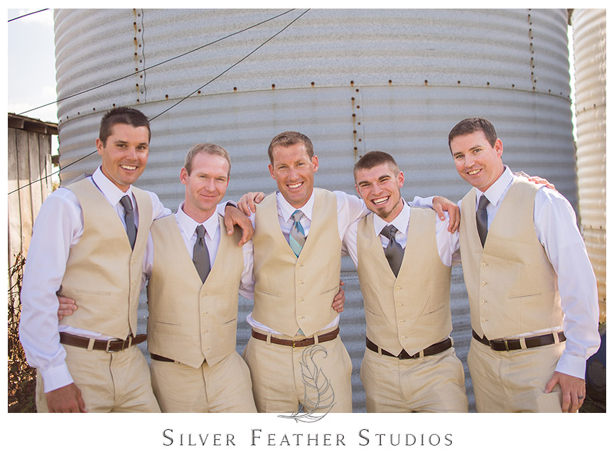 Groom and groomsmen in beige vest and pants with blue ties against a silo at Burllngton, North Carolina.  © Silver Feather Studios