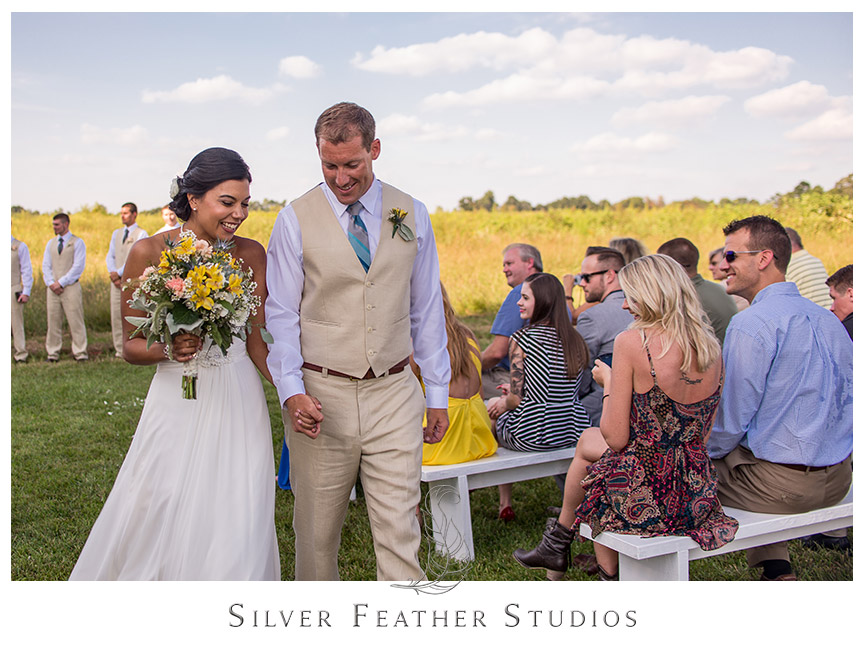 Groom escorts his new wife up the aisle after their outdoor field ceremony. © Silver Feather Studios, Burlington, NC Wedding Photography