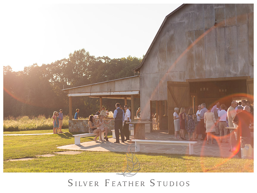 Guests fill the open and rustic barn venue at Starlight Meadow. © Silver Feather Studios, Burlington, NC Wedding Photography