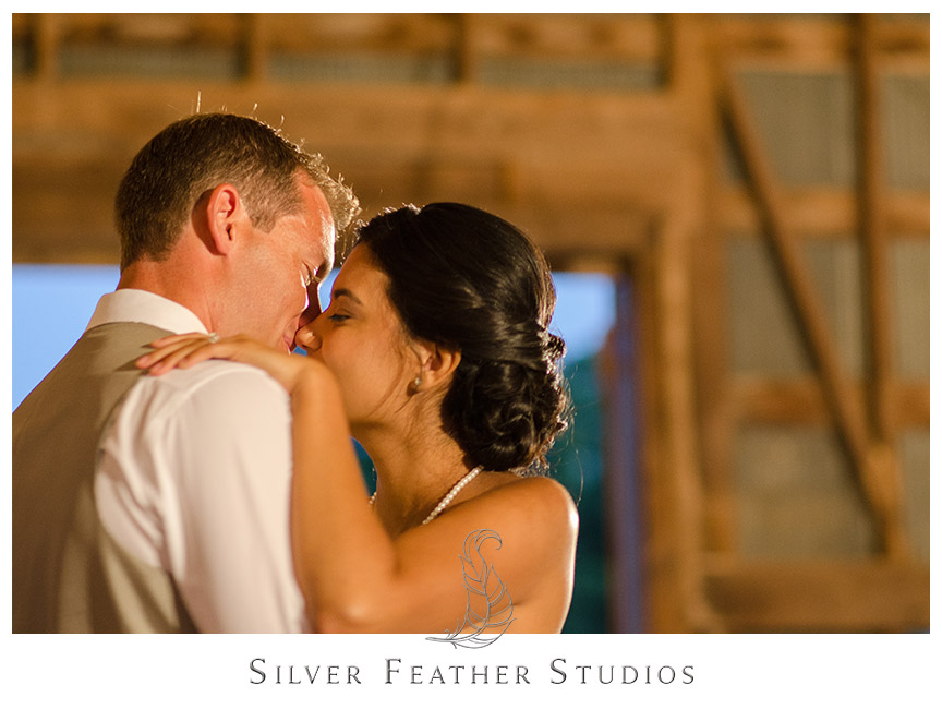 First dance under the wooden beams of this rustic barn venue at Starlight Meadow.  © Silver Feather Studios, Burlington, NC Wedding Photography