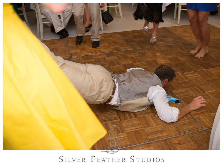 Groom does the worm at his rustic barn Starlight Meadow Wedding. First dance under the wooden beams of this rustic barn venue at Starlight Meadow.  © Silver Feather Studios, Burlington, NC Wedding Photography