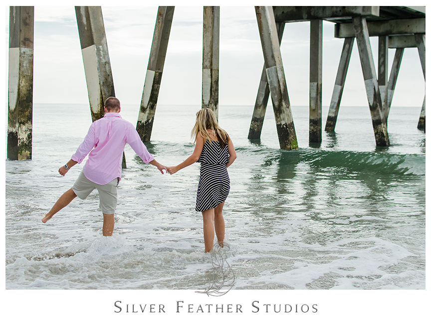 Romantic beach engagement session at Wrightsville Beach by Johnnie Mercers Fishing Pier. © Silver Feather Studios, Burlington, NC Wedding Photography & Videography