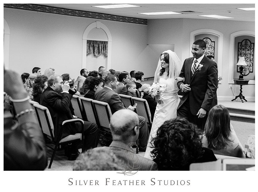 Bride and groom leave as husband and wife from their Jehovah's Witness ceremony at the Kingdom Hall of Jehovah's Witnesses. © Silver Feather Studios, Wedding Photography in Greensboro, North Carolina.