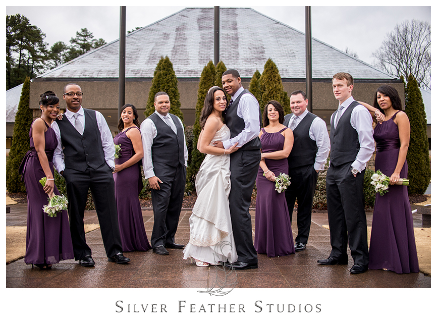 Bridesmaids wear purple floor length chiffon gowns while grooms wear black suits with grey ties at the Bryan Park Golf Center. © Silver Feather Studios, Wedding Photography in Greensboro, North Carolina.