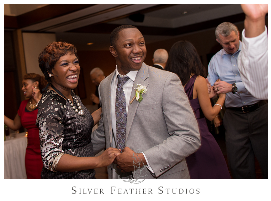 Guests dance at this purple and gray Bryan Park Golf Center Wedding reception. © Silver Feather Studios, Wedding Photography in Greensboro, North Carolina.