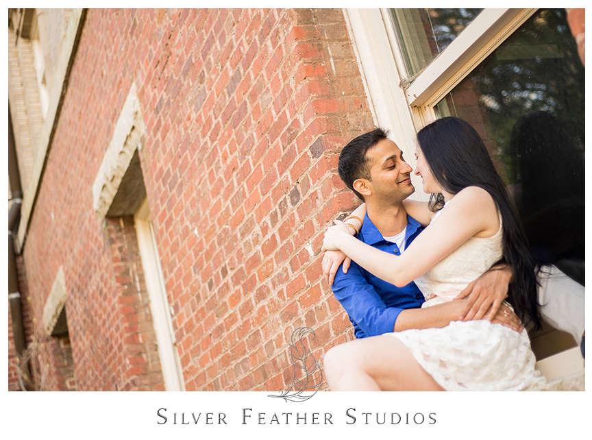 Madison and Harsh pose in the window of a UNC Chapel Hill building in their ivory and blue engagement session outfits. © Silver Feather Studios, Chapel Hill Wedding Photography & Cinematography