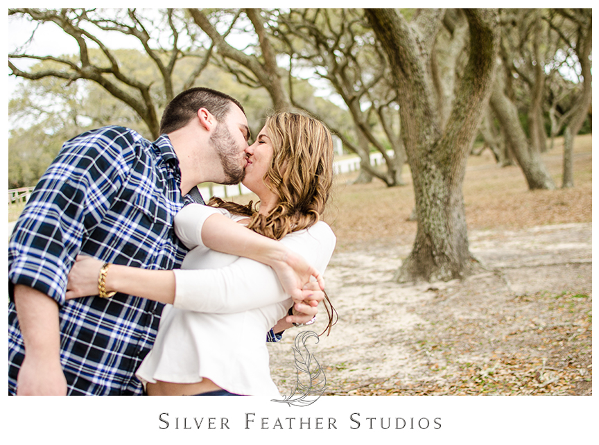 Andrew wears an blue plaid shirt with jeans at her engagement session at Fort Fisher in Kure Beach, NC. © Silver Feather Studios, Burlington, NC Wedding photography and cinematography.