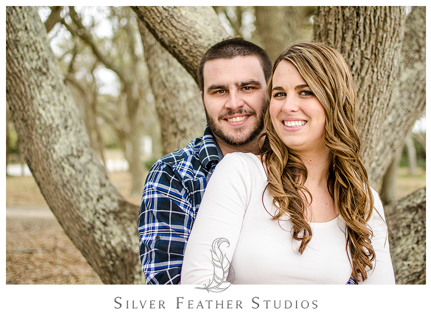 Jessica wears an ivory peplum shirt with blue jeans looks fabulous next to Andrew in his blue plaid shirt at her Fort Fisher engagement session in Kure Beach, NC. © Silver Feather Studios, Burlington, NC Wedding photography and cinematography.