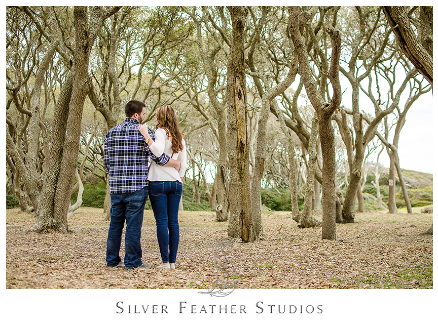 Jessica  in an ivory peplum shirt with blue jeans looks fabulous next to Andrew in his blue plaid shirt at her Fort Fisher engagement session in Kure Beach, NC. © Silver Feather Studios, Burlington, NC Wedding photography and cinematography.