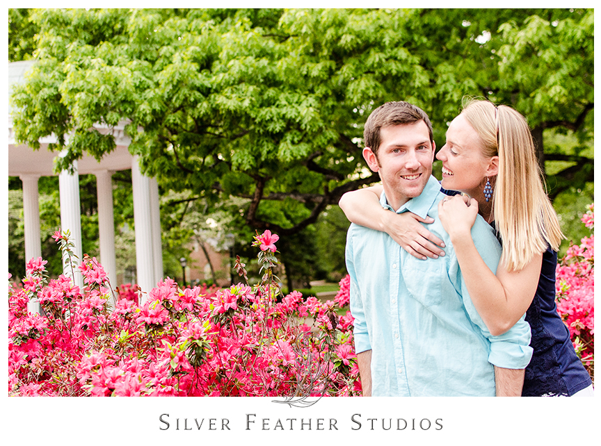 Azaleas are in full bloom by the Old Well in Chapel Hill during this fun and modern engagement photography session with Chapel Hill wedding photographer Silver Feather Studios.