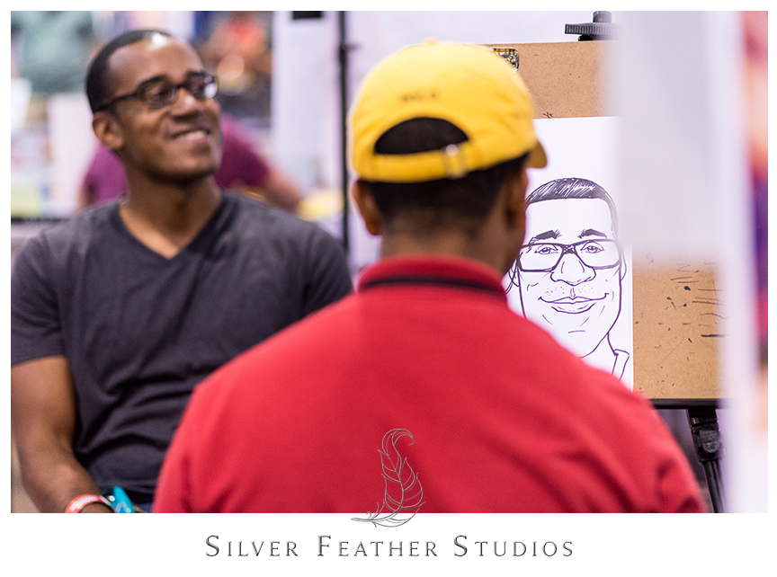 Brian poses for his caricature from 2014 Heroes Convention in Charlotte, North Carolina.© Silver Feather Studios, totally geeky wedding photographers.