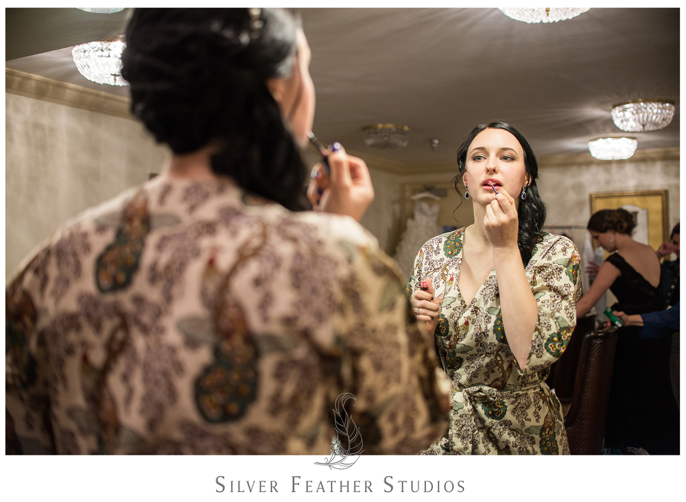 Madison puts her makeup on in Greensboro, North Carolina in the bridal suite of the Empire Room. © Silver Feather Studios, Burlington, North Carolina wedding videography and photography.