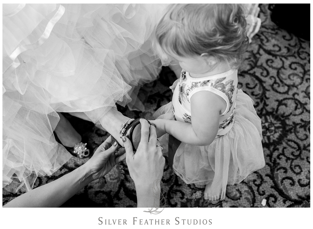 Little girl helps the bride put on her stunning blue shoes for her wedding in Greensboro North Carolina. © Silver Feather Studios, Greensboro wedding photography and videography.