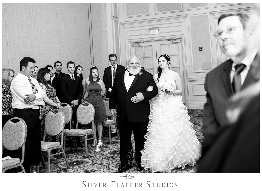 Nothing but smiles and tears as the bride walks down the aisle of the Empire Room in Greensboro, as photographed by Ariana Watts, Burlington, NC wedding photographer.
