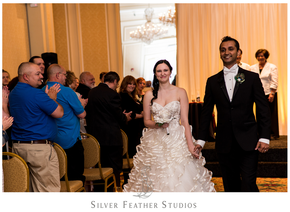 Love the happy smiles of the new Mr. and Mrs. Upadhyay as they leave their Empire Room wedding ceremony. © Silver Feather Studios, Greensboro wedding photography and videography.