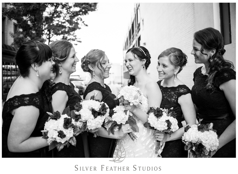 Bridesmaid wear stunning black lace floor-length gowns at this lace and feather inspired Empire Room wedding in Greensboro. © Silver Feather Studios, Burlington, NC wedding photography and videography.