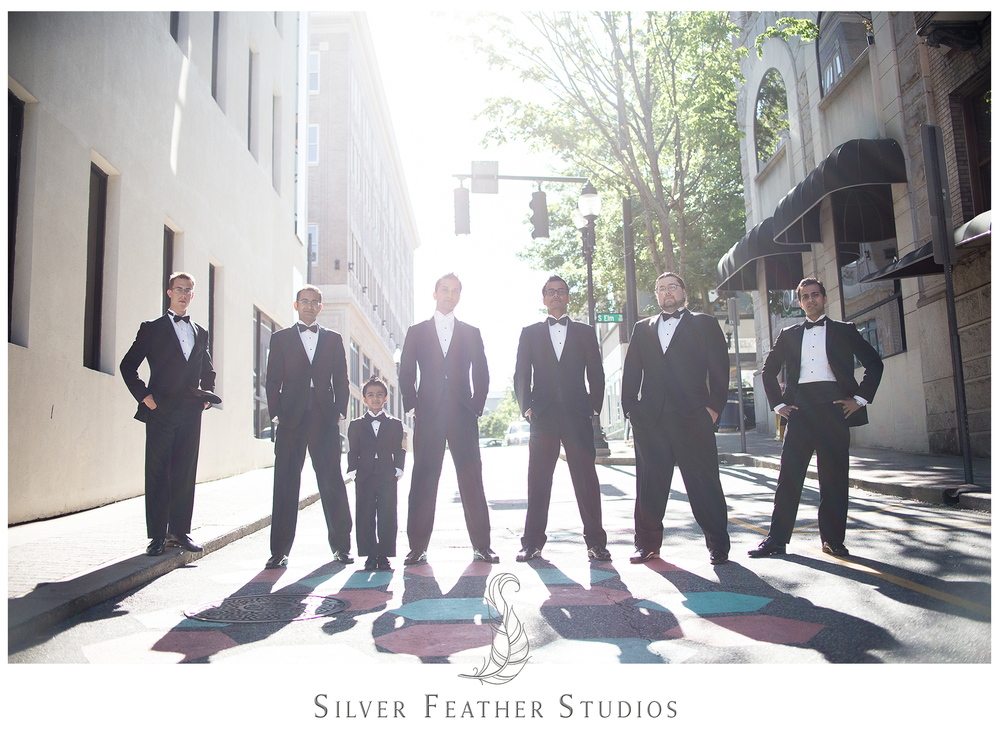 Groomsmen look handsome in black formal tuxedoes and black bow ties for Harsh's Empire Room wedding in Greensboro. © Silver Feather Studios, Burlington, NC wedding photography and videography.
