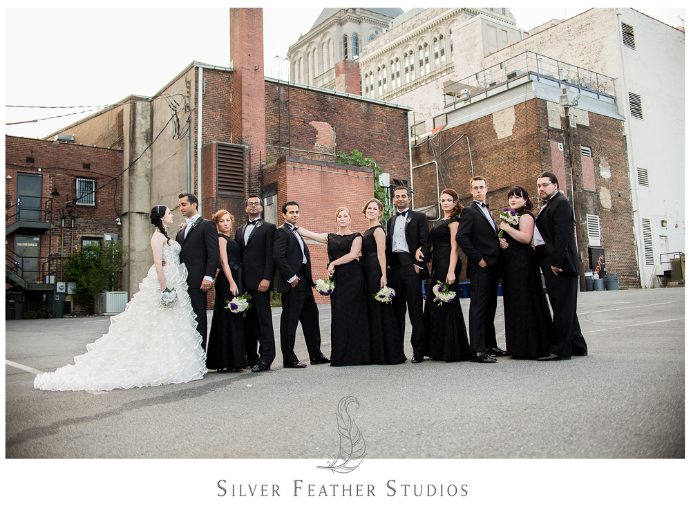 A stunning bridal party photo in downtown Greensboro, North Carolina. Photographed by Ariana Watts of Silver Feather Studios, a Burlington, NC wedding photography and videography company.