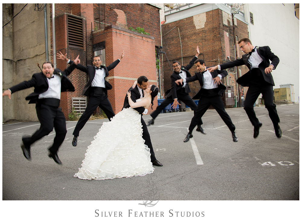The groomsmen jump in the air in their black tuxedoes as Madison and Harsh kiss after their Empire Room wedding ceremony. © Silver Feather Studios, Greensboro wedding photography and videography.