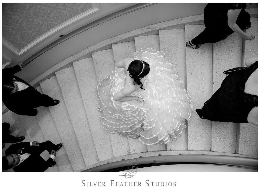 Bride walks up the staircase at the Empire Room in her full wedding gown.Photographed by Ariana Watts of Silver Feather Studios, a Burlington, NC wedding photography and videography company.