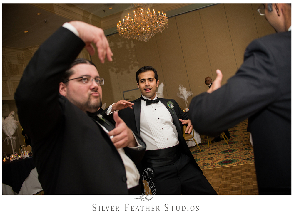 Groomsmen make strange faces and hand gestures as they dance at this Empire Room wedding reception. © Silver Feather Studios, Greensboro wedding photography and videography.