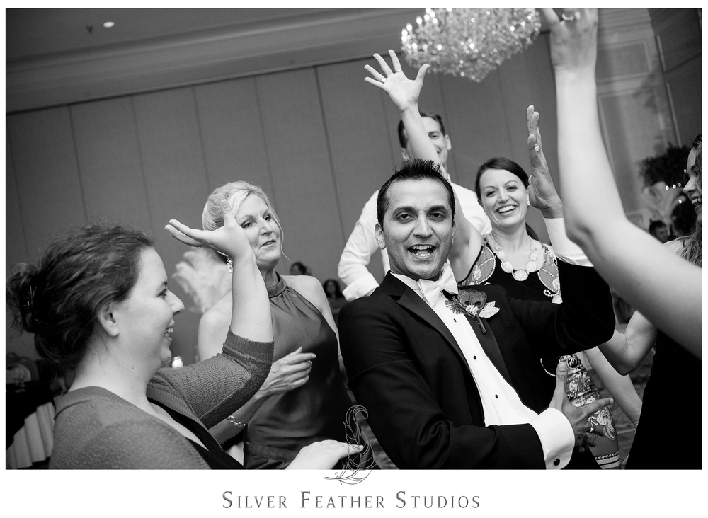 Harsh is surrounded by the ladies as he dances with friends at his Empire Room wedding reception. Photographed by Burlington wedding photographers, Silver Feather Studios.