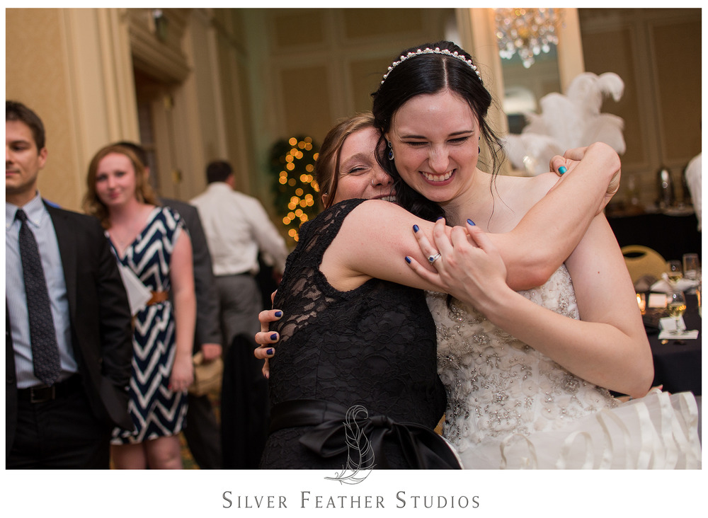 Bride hugs her bridesmaids at her wedding in Greensboro, NC. © Silver Feather Studios, Greensboro wedding photography and videography.